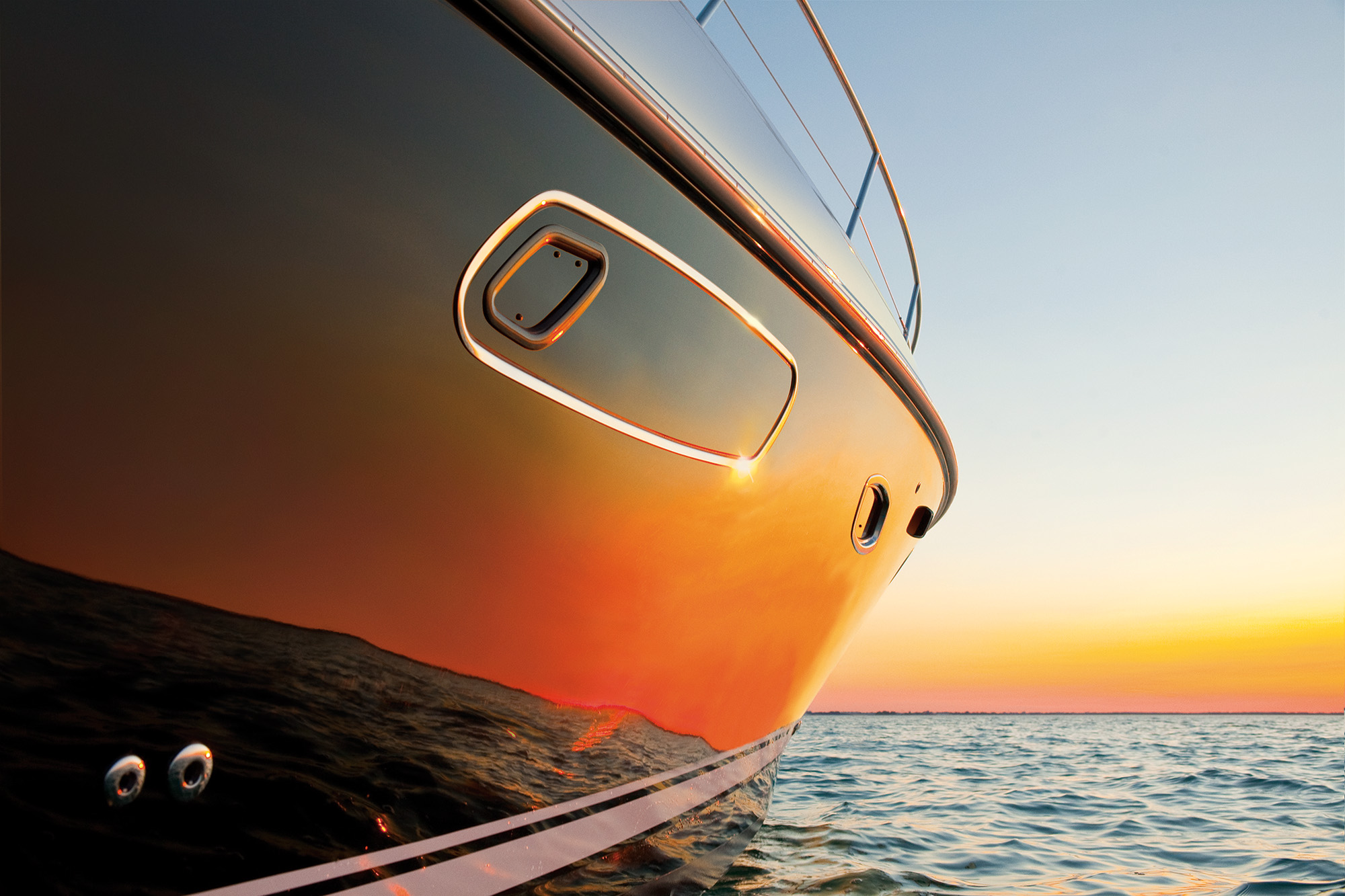 A bright orange sunset, reflected in the hull of a motorboat